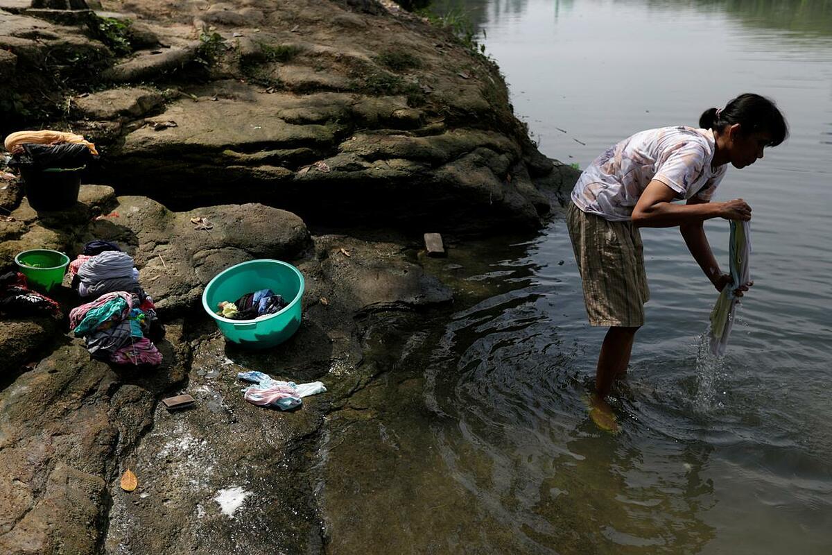 Eka Purwanti, một người dân địa phương, giặt đồ trên sông Cisadane, thành phố Tangerang, tỉnh Banten, Indonesia, hôm 2/8. Ảnh: Reuters.
