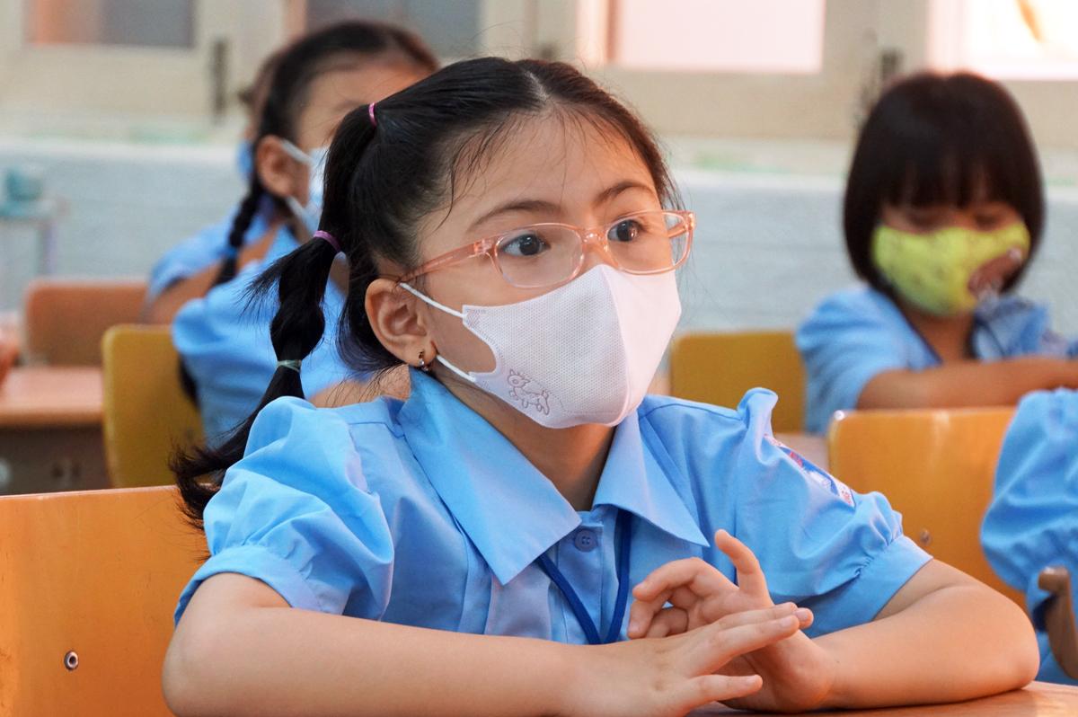 Học sinh lớp 1/4 trường Tiểu học Đinh Tiên Hoàng lắng nghe cô giáo hướng dẫn kỹ năng phòng chống Covid-19 trong ngày đầu tập trung. Ảnh: Mạnh Tùng