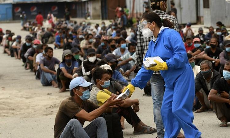 Tình nguyện viên phát thức ăn cho người dân tại khu vực bị áp hạn chế ngăn Covid-19 ở Kathmandu, Nepal hôm 31/8. Ảnh: AFP.