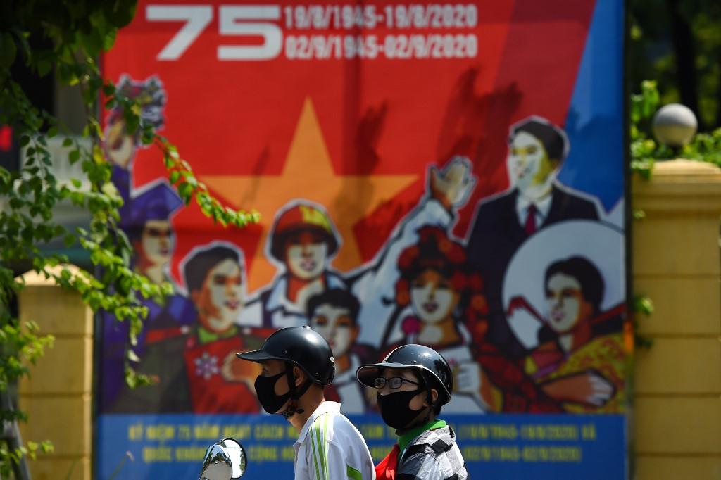 Hai thanh niên đi qua áp phích chào mừng ngày Quốc khánh hôm 1/9. Ảnh: AFP.