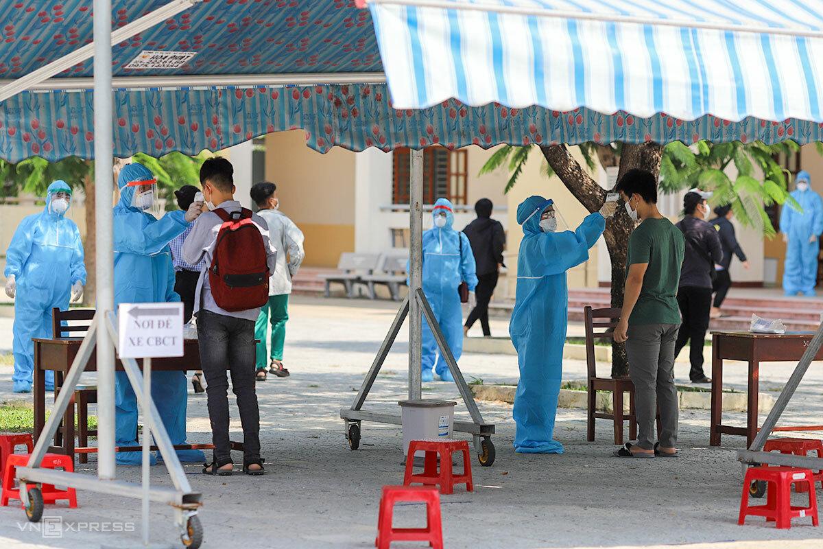 Các thí sinh được đo thân nhiệt, thay khẩu trang trước khi vào phòng thi ở trường THPT Võ Chí Công. Ảnh: Nguyễn Đông.