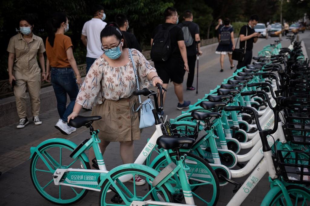 Một phụ nữ sử dụng xe đạp công cộng trong giờ cao điểm ở Bắc Kinh, Trung Quốc, hôm 2/9. Ảnh: AFP.
