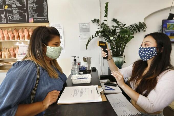 Nhân viên đo thân nhiệt cho khách tại tiệm Captivate Nail & Spa ở thành phố Fullerton, bang California, hôm 19/6. Ảnh: LA Times.