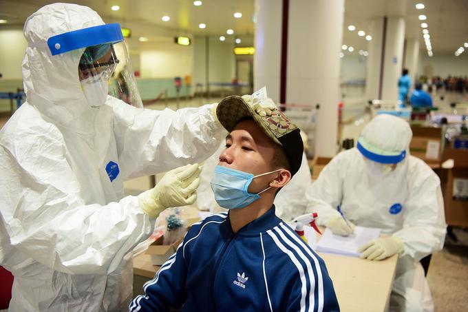 Cán bộ y tế lấy mẫu bệnh phẩm của từng người tại sân bay nội bài để xét nghiệm, ngày 18/3. Ảnh: Giang Huy