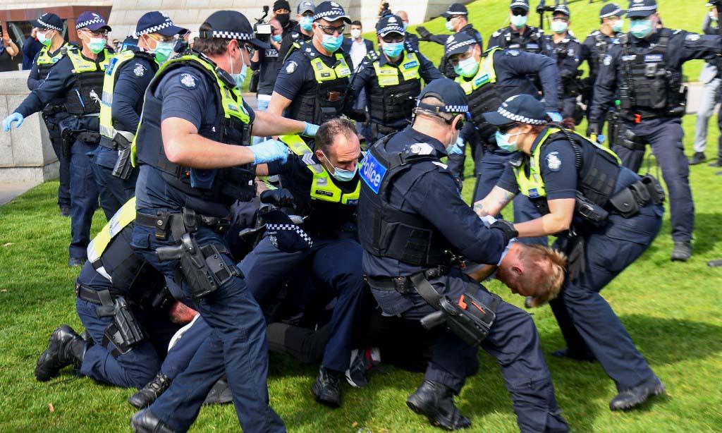 Cảnh sát không chế người biểu tình tại thành phố Melbourne, Australia, hôm nay. Ảnh: AFP.