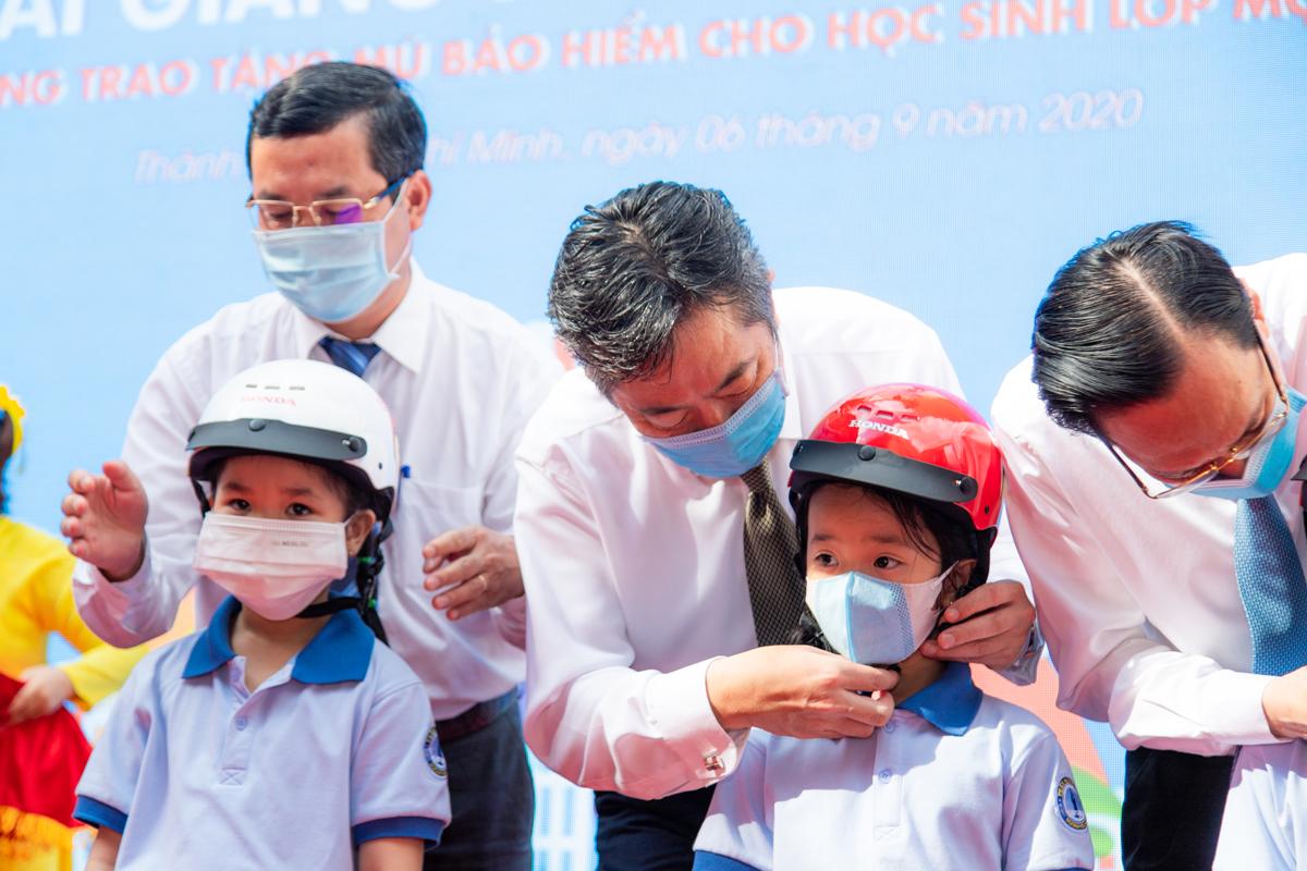 Các đại diện tham dự sự kiện hướng dẫn đeo mũ bao hiểm cho học sinh.