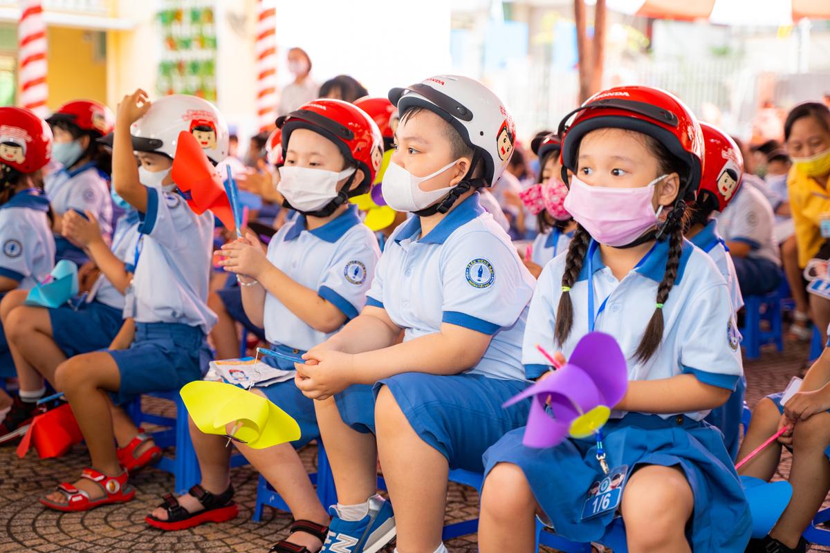 Học sinh lớp Một trường tiểu học Trần Hưng Đạo, quận 1, TP HCM nhận mũ bảo hiểm trong ngày khai giảng.