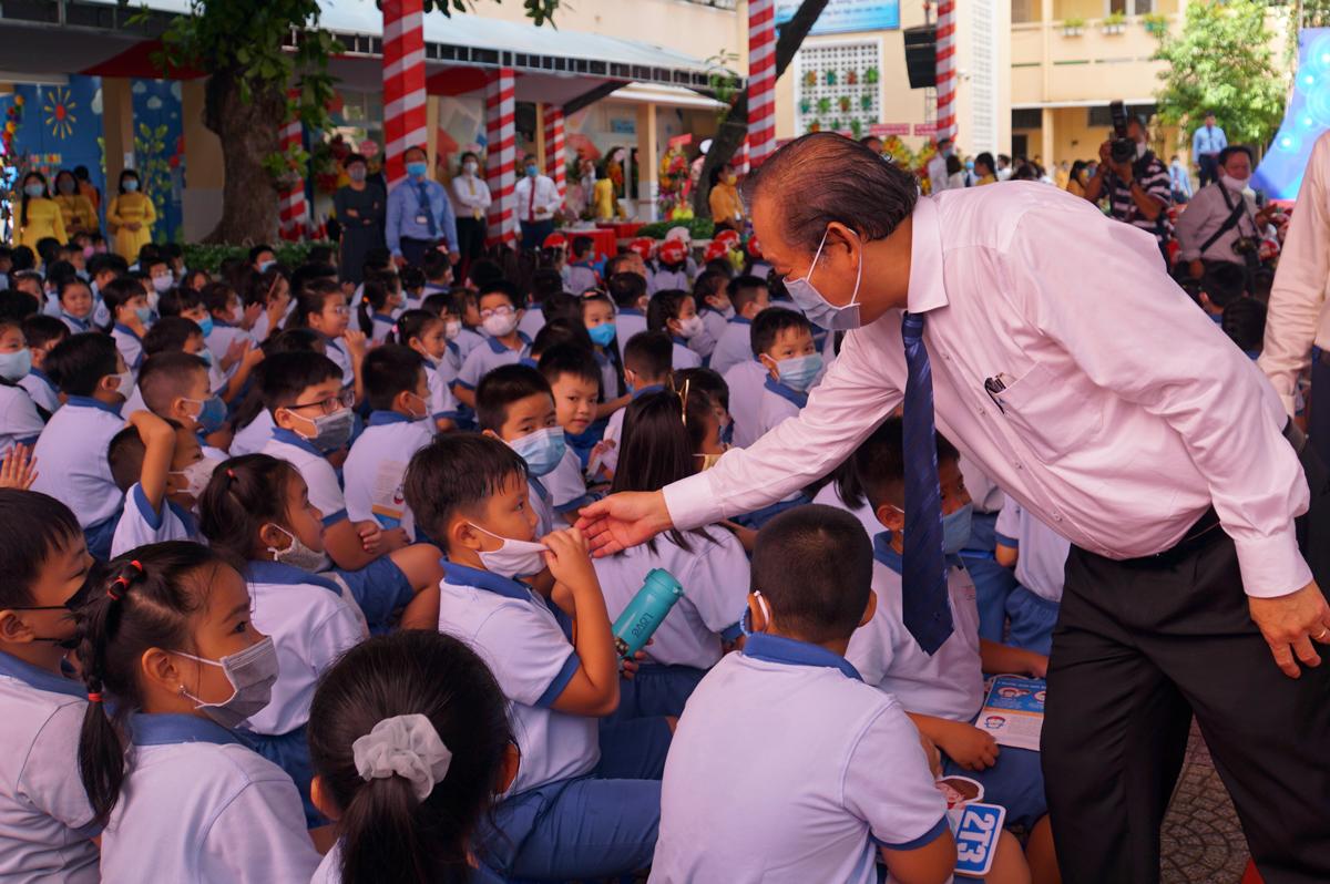 Phó thủ tướng Trương Hoà Bình nhắc một học sinh đeo khẩu trang đúng cách. Ảnh: Mạnh Tùng