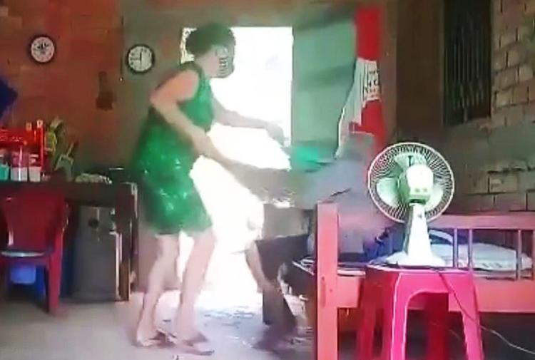 Cảnh bà Hoa đổ rác lên người mẹ ruột. Ảnh: Cắt từ video do Bùi Thanh Tuyền quay.