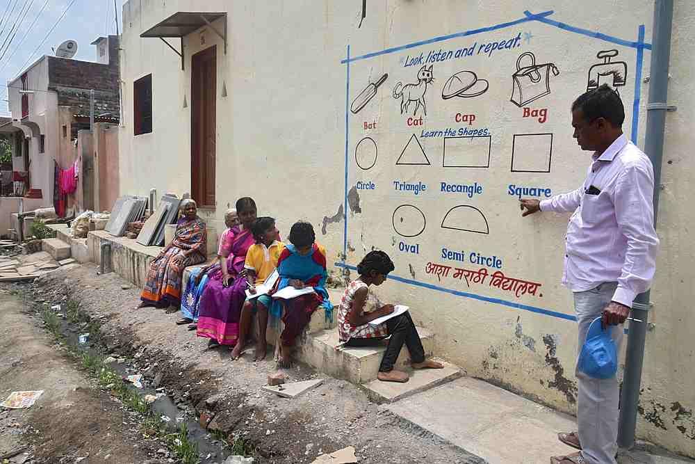 Kalidas Chavdekar, giáo viên trường Asha Marathi Vidyalaya dạy học sinh từ mới tiếng Anh qua tranh tường. Ảnh: AFP.