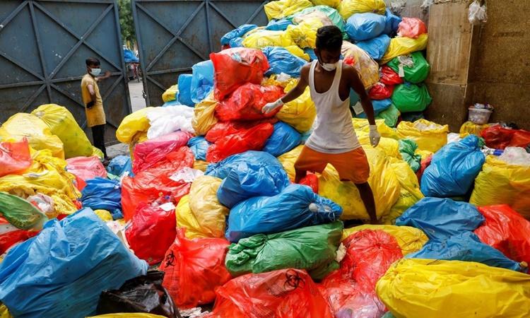 Người thu gom rác bước đi trên những túi nylon rác thải y tế chưa được xử lý bên ngoài một bệnh viện ở New Delhi, Ấn Độ, hồi tháng 7. Ảnh: Reuters.