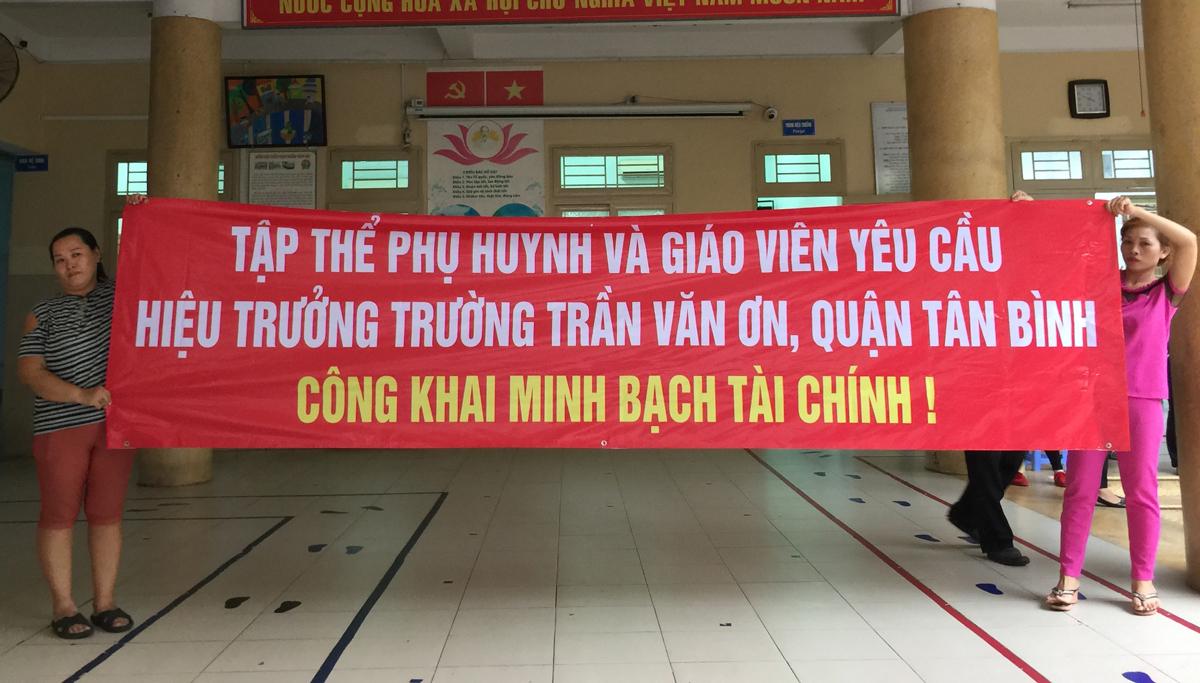 Phụ huynh trường Tiểu học Trần Văn Ơn (quận Tân Bình) căng băng rôn yêu cầu hiệu trưởng minh bạch thu chi tài chính, chiều 30/6. Ảnh: Mạnh Tùng