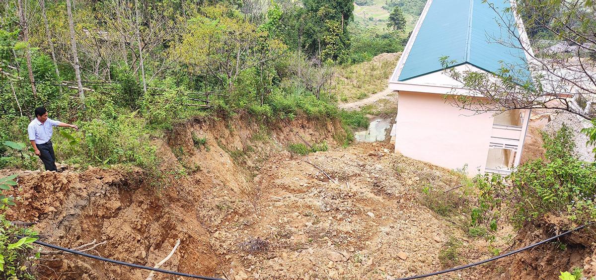 Sườn núi sau trường có một cung sạt trượt kéo dài, tiềm ẩn nguy cơ mất an toàn trong mùa mưa lũ. Ảnh: Lam Sơn.
