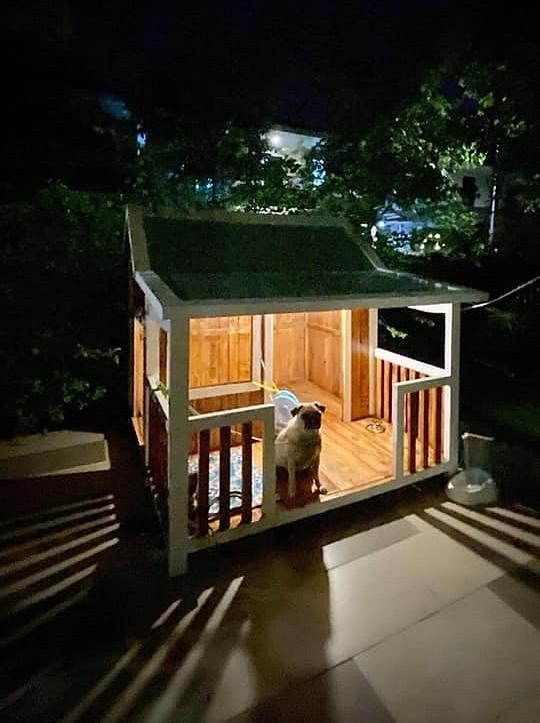 Cậu ấm sở hữu một ngôi nhà riêng bằng gỗ, có phòng ngủ bên trong và mái hiên lắp đèn sáng trưng. Bên trong lấp ló chiếc quạt mát, có cả lan can ngồi ngắm cảnh khá chill.