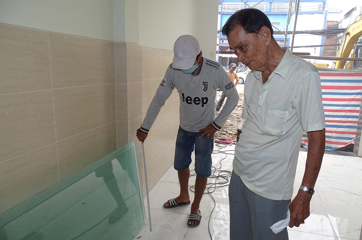 Ông Trần Văn Đức đang cùng thợ sửa nhà sau khi bàn giao mặt bằng cho dự án Metro Số 2, ngày 12/9. Ảnh: Hà An.