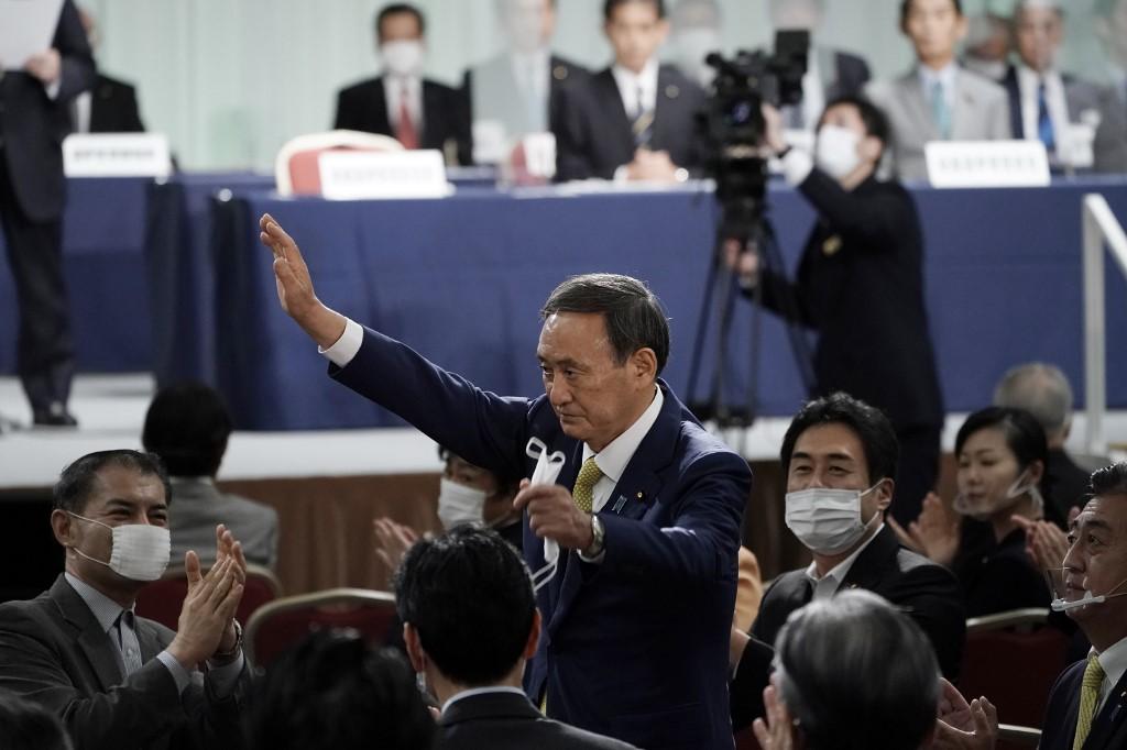 Ông Suga giơ tay ăn mừng sau khi kết quả bầu tân chủ tịch LDP được công bố hôm nay. Ảnh: AFP.