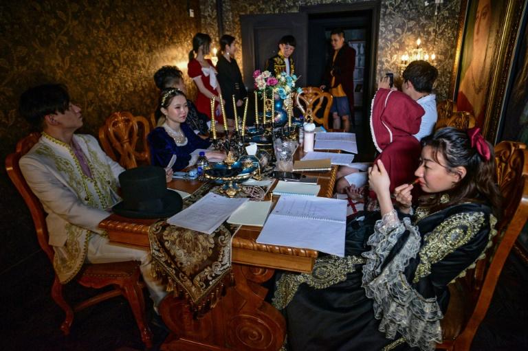 Nhóm bạn trẻ chuẩn bị tham gia trò chơi giải mã án mạng bí ẩn Biệt thư Ma ám tại một studio game ở Thượng Hải hôm 13/8. Ảnh: AFP.
