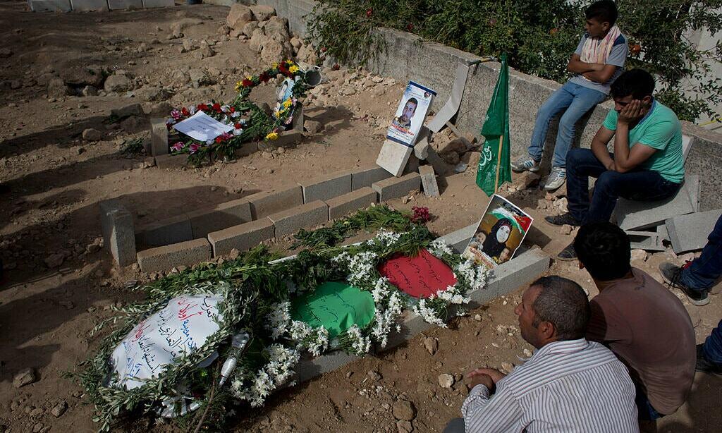 Người Palestine ngồi bên ngôi mộ của gia đình Dawabsheh năm 2015. Ảnh: AP.