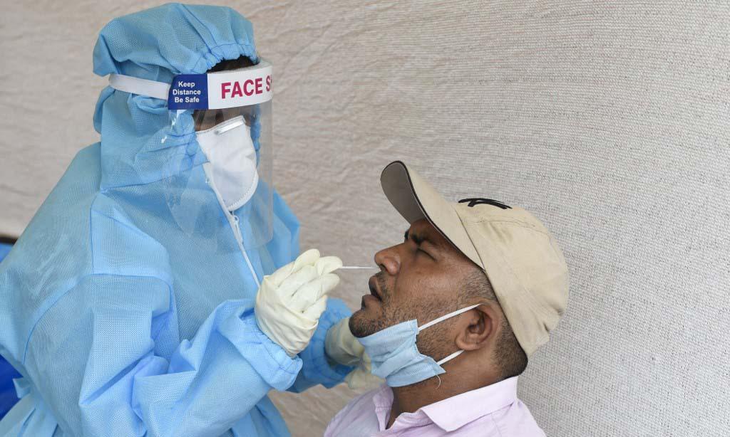 Nhân viên y tế lấy mẫu xét nghiệm nCoV cho người dân tại thành phố Ahmedabad, Ấn Độ, hôm 14/9. Ảnh: AFP.