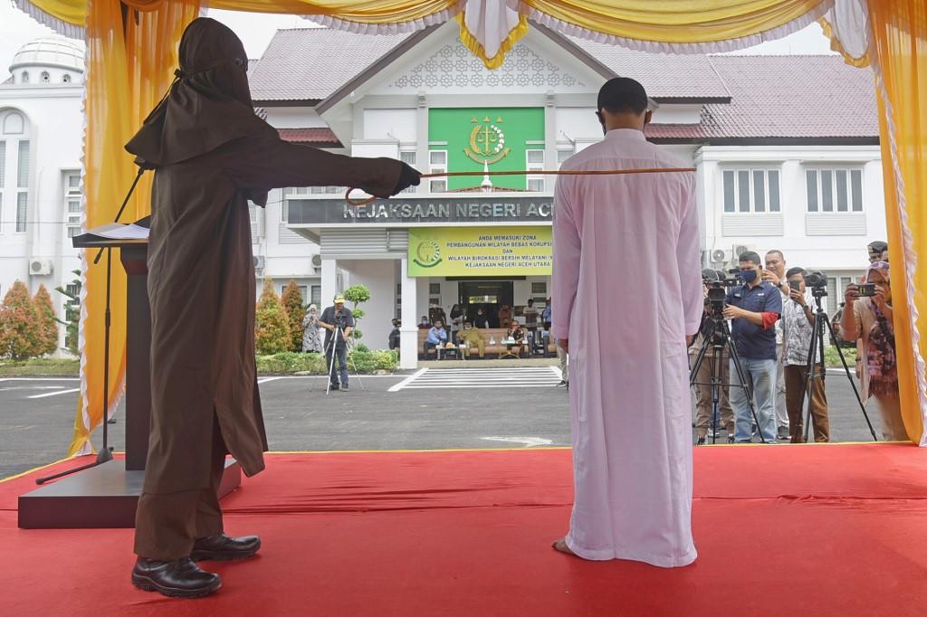 Người quan hệ với trẻ vị thành niên (áo trắng) bị phạt đánh hơn 100 roi ở Lhokseumawe, Bắc Aceh, hôm 15/9. Ảnh: AFP.