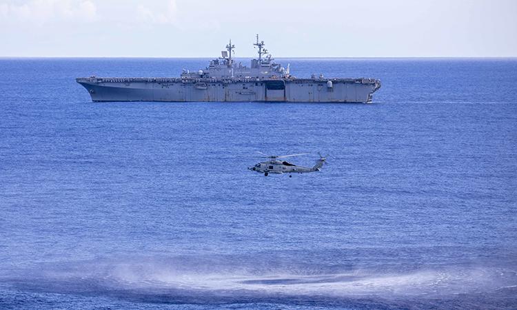 Trực thăng MH-60R thả đầu dò thủy âm xuống nước trong diễn tập săn ngầm với tàu sân bay trực thăng  USS Wasp (phía sau), ngày 13/9. Ảnh: US Navy.