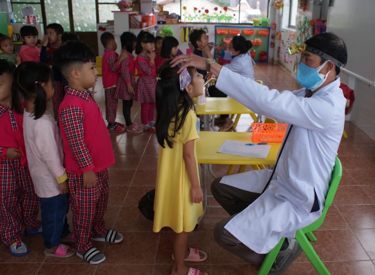 Bác sĩ khám sàng lọc trẻ mầm non trường Anh Đào để phòng bệnh Tay chân miệng. Ảnh: Khánh Hương