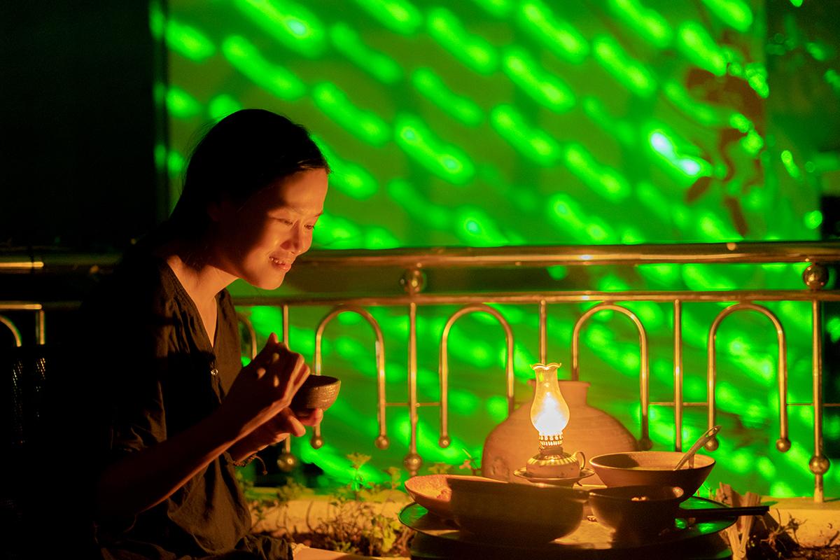 Chị Mai Tuyết dùng cơm bên đèn dầu. Ảnh: Võ Thạnh