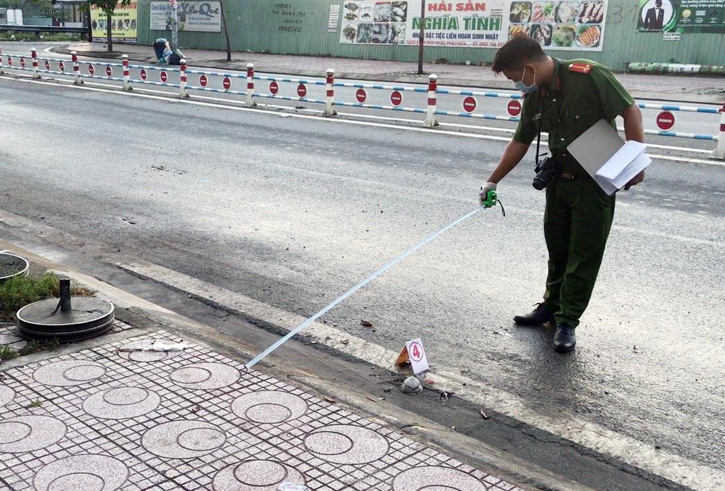 Cảnh sát khám nghiệm đoạn đường xảy ra vụ truy sát làm một người chết. Ảnh: Đình Văn.