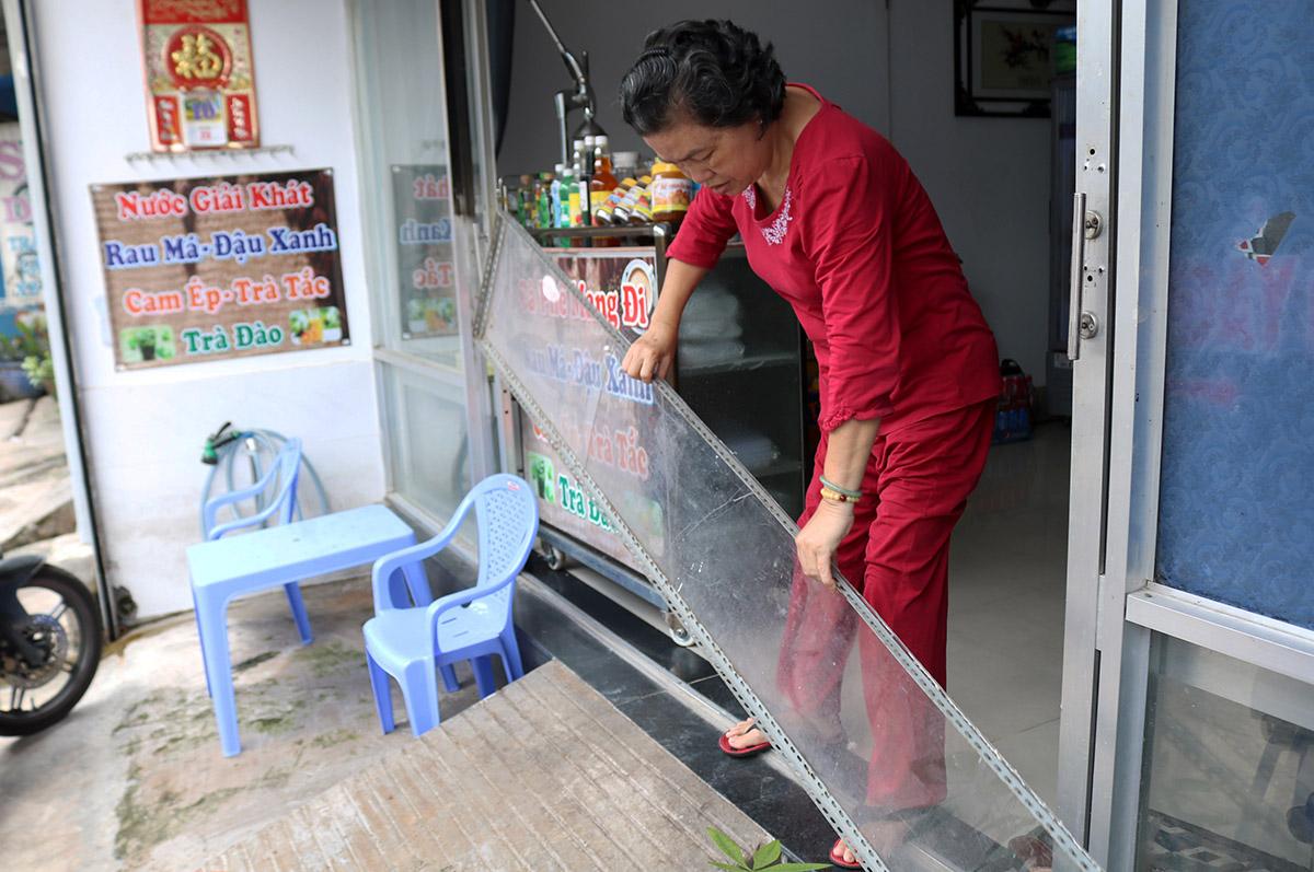 Bà Đặng Thị Hương cho biết dù đã nâng cao nền nhà khoảng nửa mét so với mặt đường nhưng vẫn phải phòng thủ thêm tấm ván, sáng 12/9. Ảnh: Gia Minh.