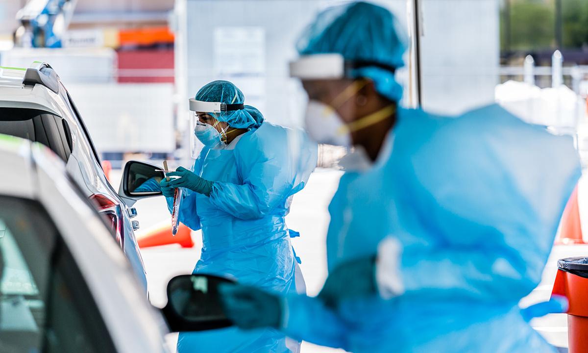 Nhân viên y tế lấy mẫu xét nghiệm nCoV trên xe ở Tulsa, bang Oklahoma hồi tháng 7. Ảnh: NYTimes.