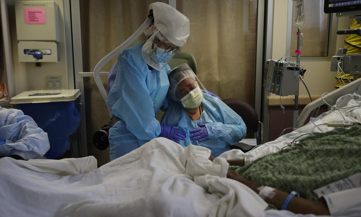 Romelia Navarro (phải) khóc khi chứng kiến chồng sắp qua đời vì Covid-19 tại Trung tâm Y tế St. Jude ở Fullerton, bang California hôm 31/7. Ảnh: AP.
