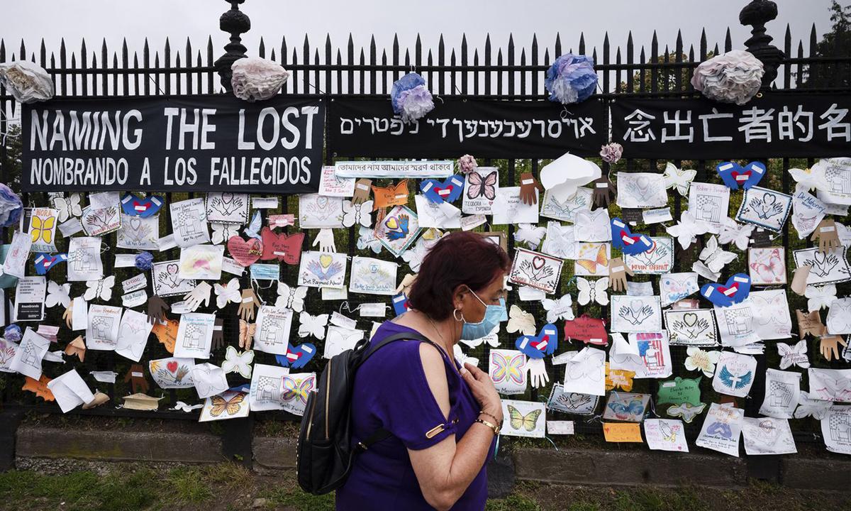 Người phụ nữ đi qua bức tường tưởng niệm người chết vì Covid-19 ở nghĩa trang Green-Wood, hạt Brooklyn, thành phố New York hôm 28/5. Ảnh: AP.