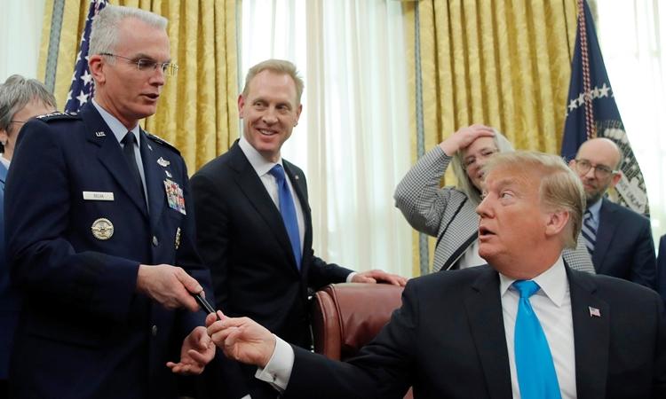 Tổng thống Mỹ Donald Trump (phải) trao bút cho tướng Paul Selva (trái) tại Nhà Trắng, tháng 2/2019. Ảnh: Reuters.