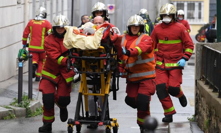 Lính cứu hỏa đưa người bị thương rời hiện trường vụ đâm dao gần văn phòng cũ của tạp chí Charlie Hebdo, ở Paris, Pháp, hôm 25/9. Ảnh: AFP.