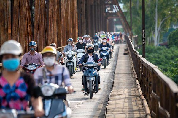 Người dân đi xe máy trên cầu Long Biên, Hà Nội. Ảnh: Bloomberg.