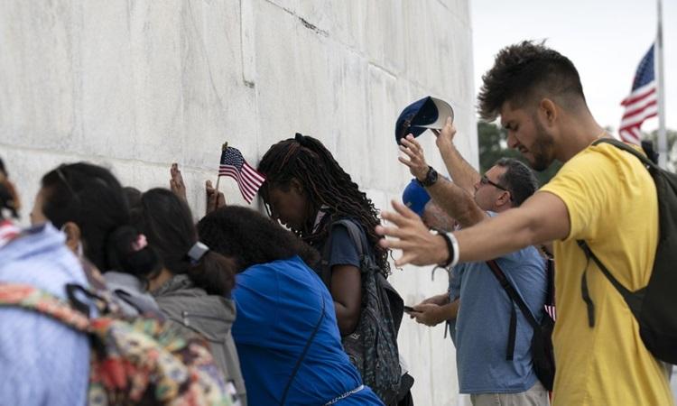 Người tham gia tuần hành cầu nguyện tại ở chân Đài tưởng niệm Washington hôm 26/9. Ảnh: AP.