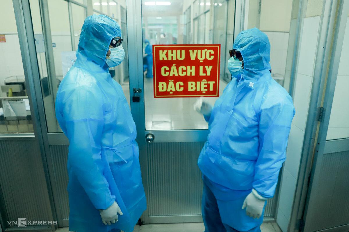 Ông Huỳnh Đức Thơ (bìa trái) mang đồ bảo hộ vào khu cách ly Bệnh viện Phổi Đà Nẵng động viên các bệnh nhân mắc Covid-19. Ảnh: Nguyễn Đông.