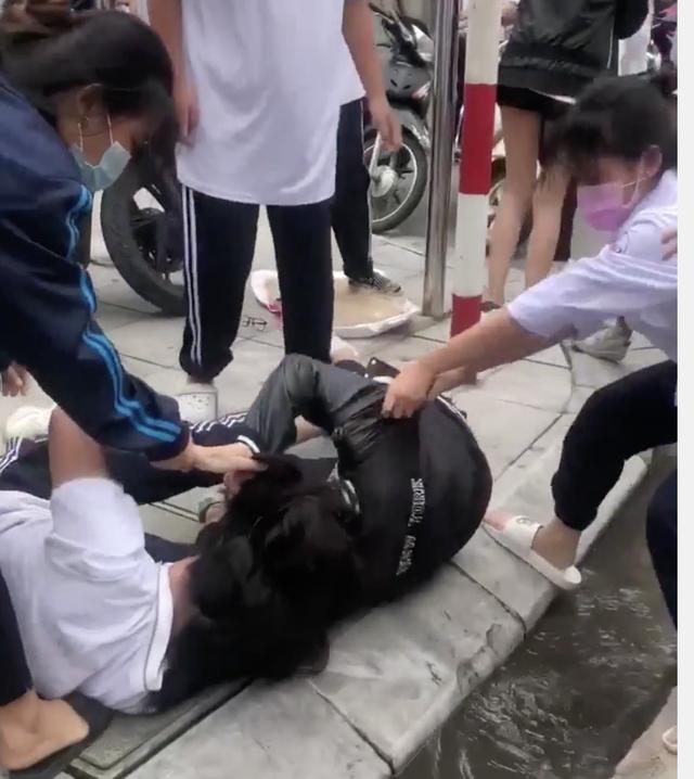 Ba nữ sinh trường THPT Huỳnh Thúc Kháng, quận Thanh Xuân, Hà Nội, đánh nhau trước cổng trường. Ảnh chụp màn hình