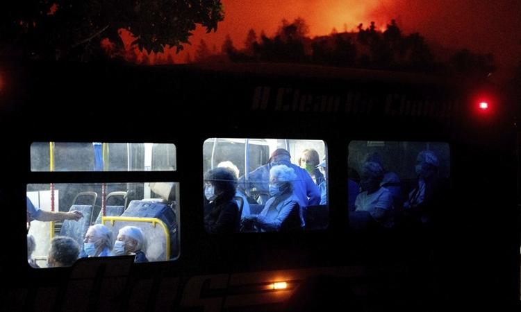Người dân ở thành phố Santa Rosa, bang California, lên xe buýt đi sơ tán khi cháy rừng bùng phát dữ dội hôm 28/9. Ảnh: AP.