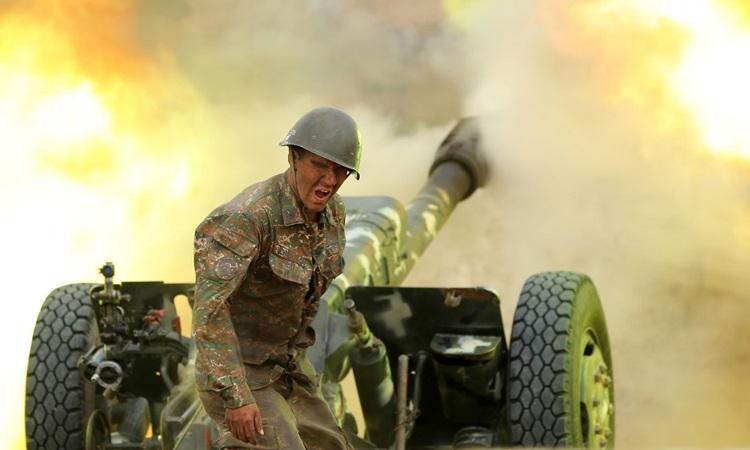 Một quân nhân của Lực lượng Quốc phòng Karabakh bắn một quả pháo về phía các vị trí của Azeri trong cuộc giao tranh tại khu vực ly khai Nagorny-Karabakh hôm 28/9. Ảnh: AFP.