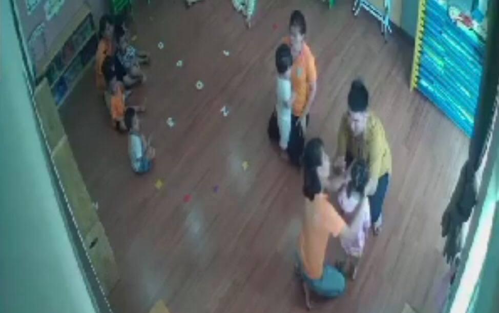 Phụ huynh (áo vàng) sau khi đánh bé gái đứng giữa lớp, quay ra dỗ dành con mình. Ảnh chụp camera lớp học.