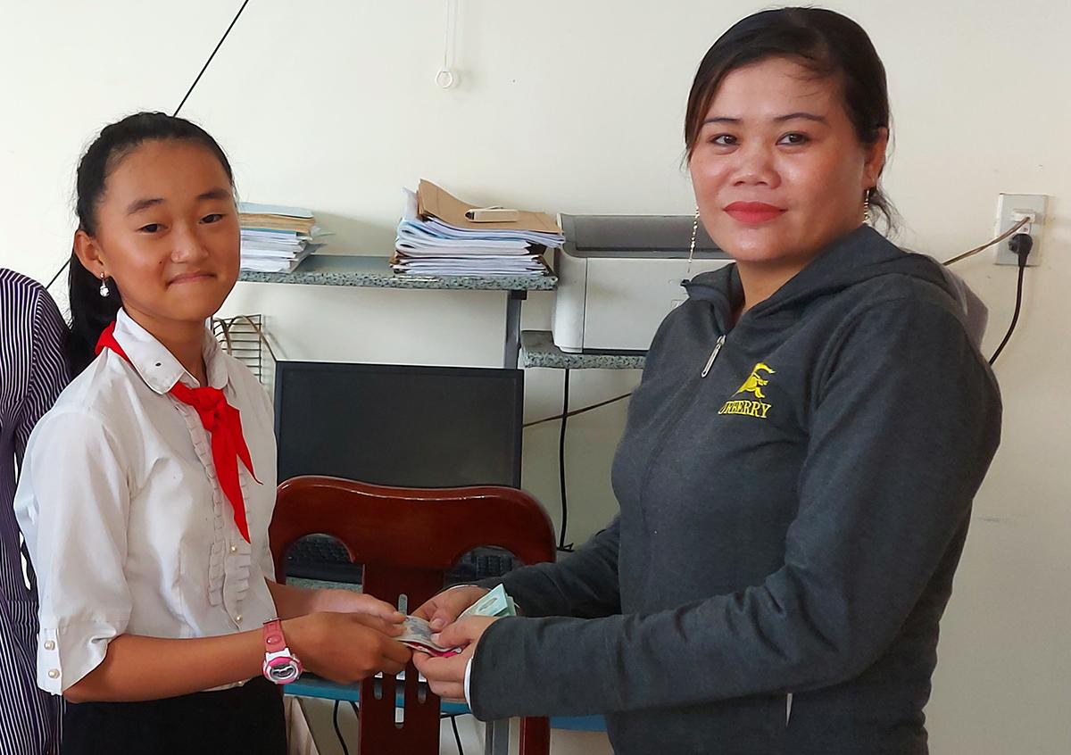 Nữ sinh Như Ý trả lại tiền nhặt được cho bà Ngọc tại công an địa phương. Ảnh: Nguyễn Chiến
