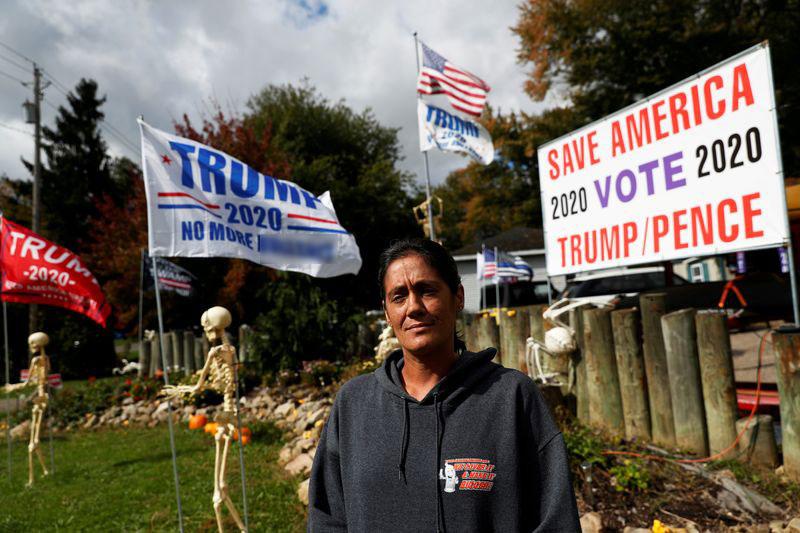 Maranda Joseph trước sân nhà trang trí Halloween và cờ Trump ở Warren, Ohio, hôm 2/10. Ảnh: Reuters.