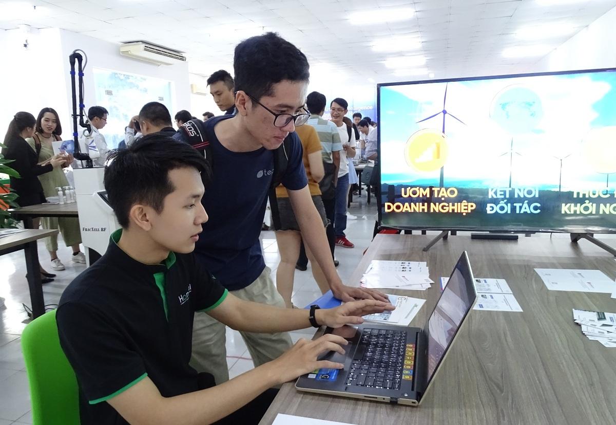 Kỹ sư về AI của doanh nghiệp khởi nghiệp giới thiệu cho một bạn trẻ về chatbot tại lễ ra mắt, sáng 3/10. Ảnh: Hà An.