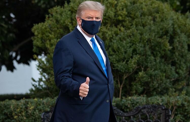 Tổng thống Trump đi bộ trên bãi cỏ Nhà Trắng để lên trực thăng vào viện ngày 2/10. Ảnh: AFP.