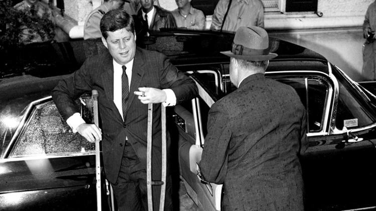 Đau lưng chỉ là một trong số những căn bệnh mạn tính đeo bám tổng thống Kennedy suốt nhiều năm. Trong ảnh, ông chống nạng để lên du thuyền tổng thống vào tháng 6/1961 để đón tiếp thủ tướng Nhật Bản. Ảnh: AP.