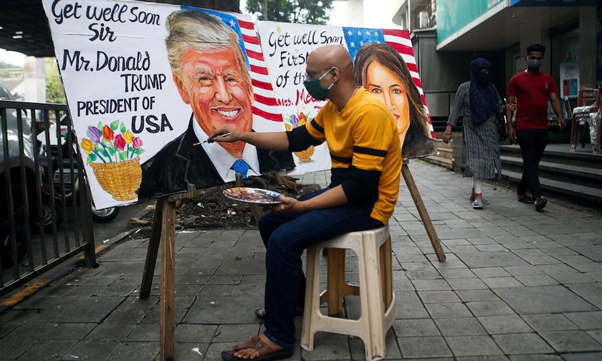 Họa sĩ Ấn Độ vẽ tranh Tổng thống Donald Trump cùng lời chúc ông sớm hồi phục tại Mumbai hôm 2/10. Ảnh: Reuters.