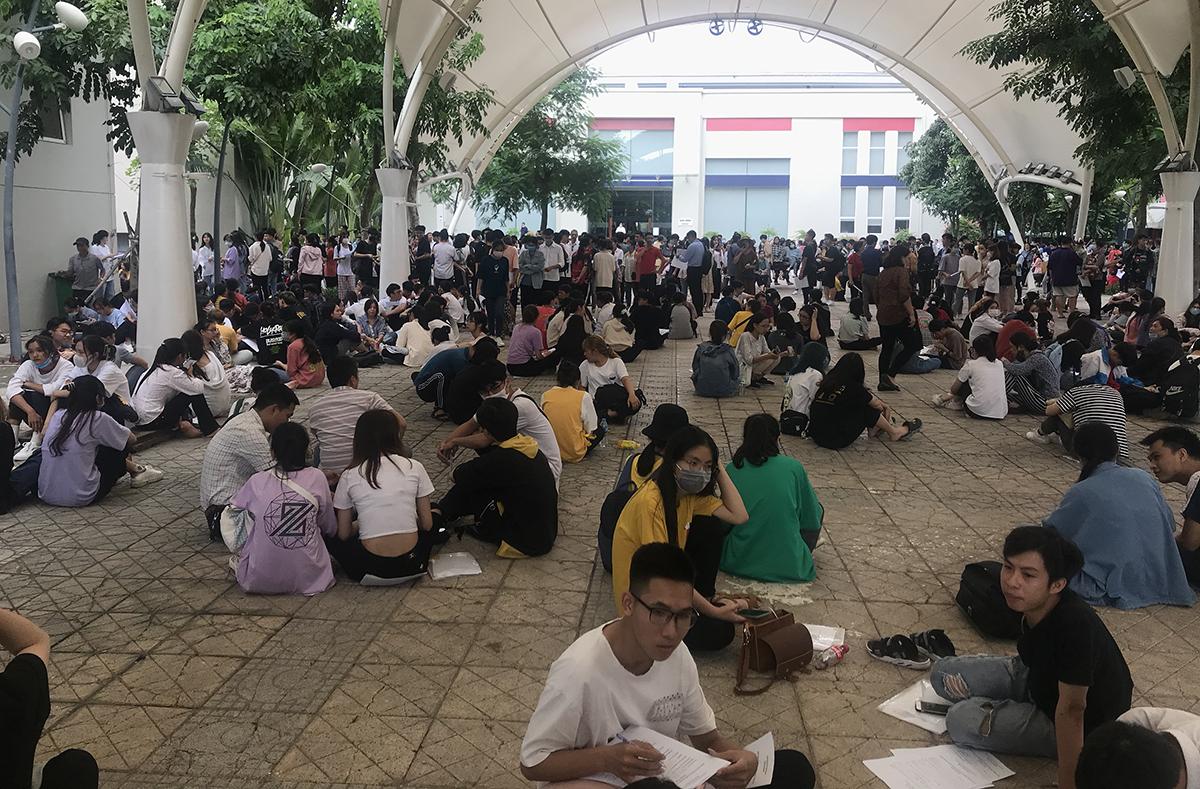 Thí sinh ngồi la liệt trong khuôn viên Đại học Thăng Long lúc 16h chiều 6/10 để đợi đến lượt nộp hồ sơ. Ảnh: Dương Tâm.