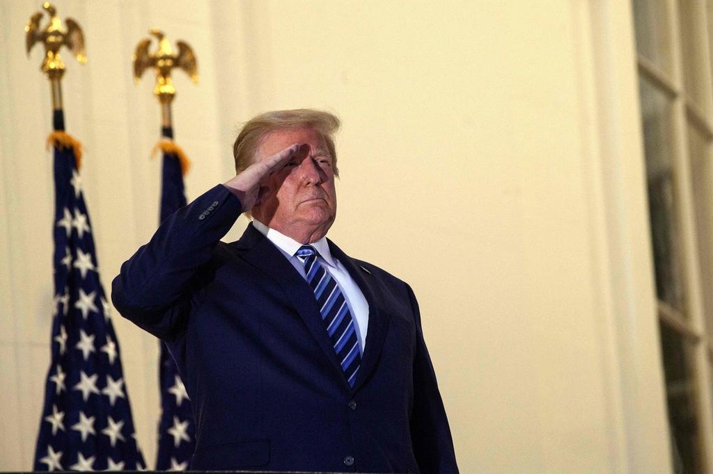 Tổng thống Trump giơ tay chào kiểu nhà binh với các sĩ quan trên trực thăng từ ban công Nhà Trắng, hôm 5/10. Ảnh: AFP.