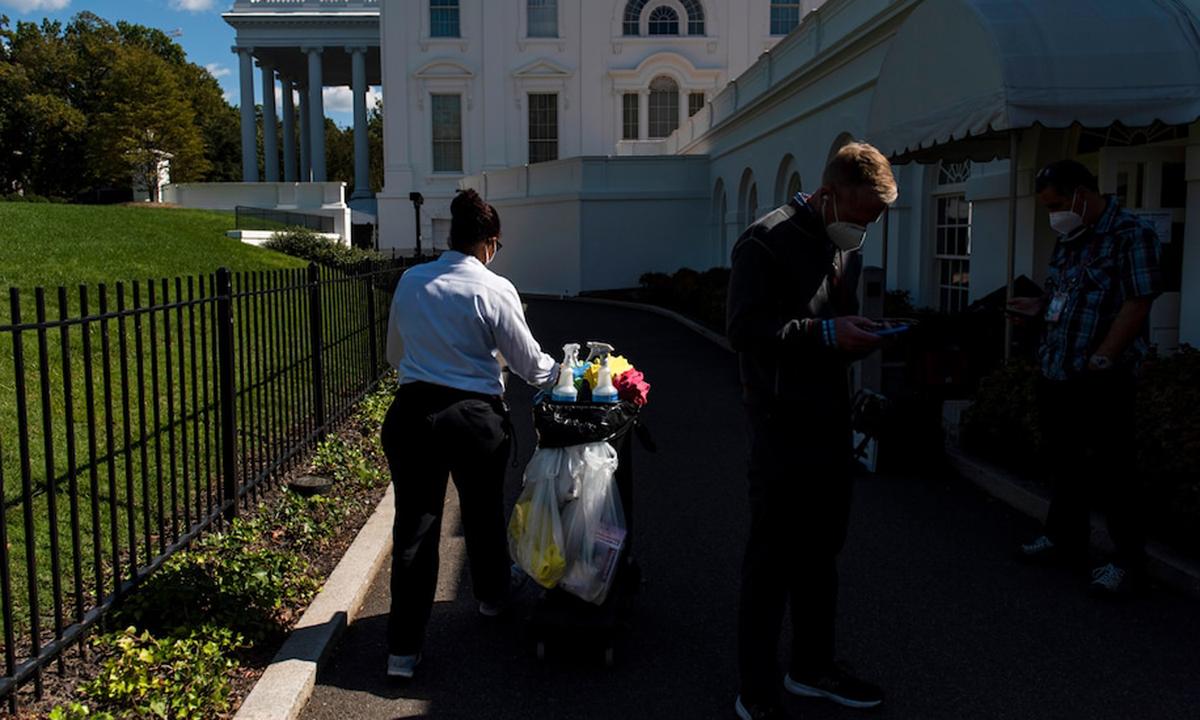 Nhân viên Nhà Trắng (trái) kéo xe chở vật dụng dọn vệ sinh bên ngoài Nhà Trắng hôm 2/10. Ảnh: Washington Post.